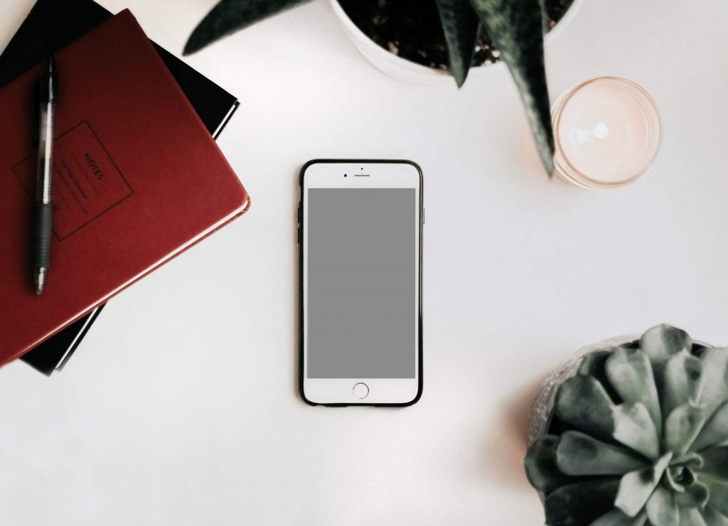 White Iphone on White desk with books and plants