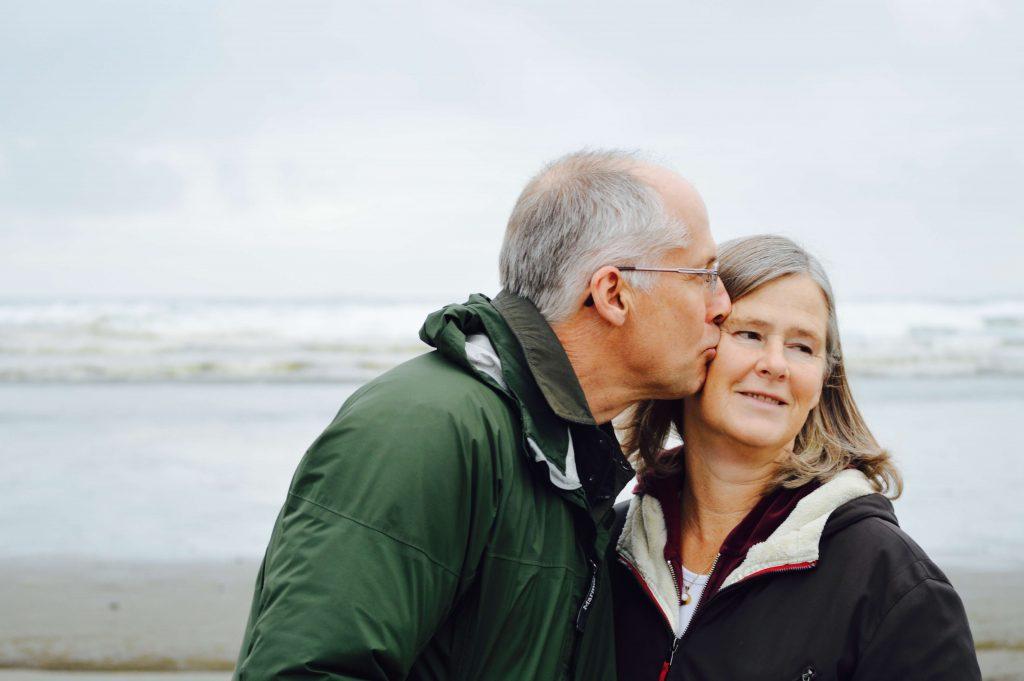 man kissing a woman on the cheek outside